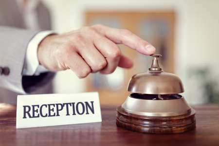 recepcion: El hombre de negocios que suena una alarma del servicio de recepción del hotel para llamar la atención