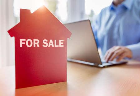Człowiek za pomocą laptopa w poszukiwaniu nieruchomości lub nowego domu w internecie na sprzedaż z napisem na czerwonym domu