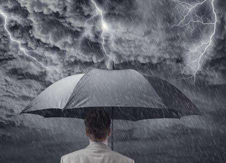 Biznesmen z czarnego biznesu parasol chroniąc się od koncepcji burzy za ubezpieczenie, ochronę finansową z recesji lub depresji gospodarczej