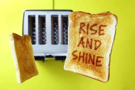 wakening: Good morning rise and shine on flying toast or toasted bread popping up from the toaster