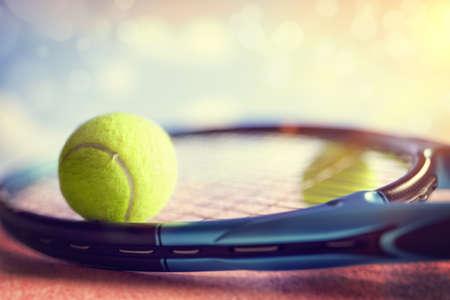 asphalt: Tennis ball resting on top of a tennis racquet on a red asphalt court