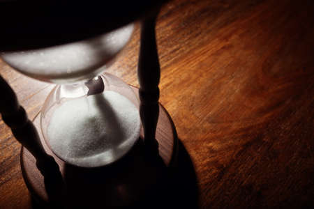 out time: Hourglass time passing concept for business deadline, urgency and running out of time
