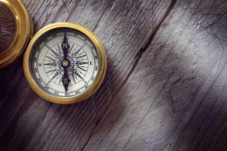 cestování: Starožitný zlatý kompas na dřevěné pozadí konceptu pro směr, cestování, navádění nebo pomoc