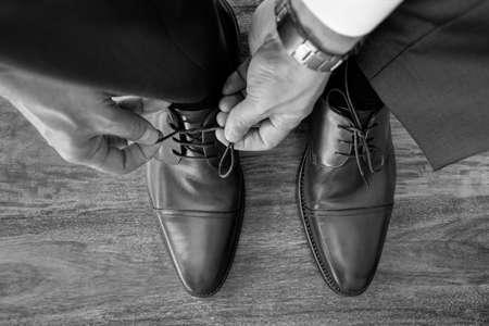 Uomo d'affari o sposo legare lacci per le scarpe che si preparano per incontri di lavoro, intervista o matrimonio