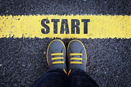 Inicio niño línea de zapatillas de deporte en pie junto a una línea de salida de color amarillo