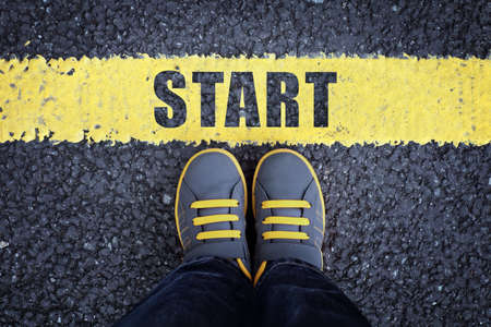 starting line: Start line child in sneakers standing next to a yellow starting line