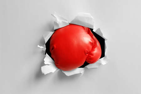 punched out: Boxing gloves knockout punch punching through torn paper hole ready for message on glove