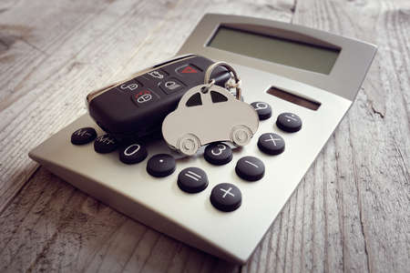 Car shape keyring and key on calculator concept for motoring costs, finance, insurance, servicing or fuel bills Stockfoto