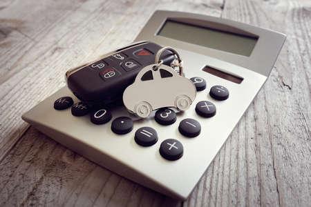 Car shape keyring and key on calculator concept for motoring costs, finance, insurance, servicing or fuel bills Foto de archivo