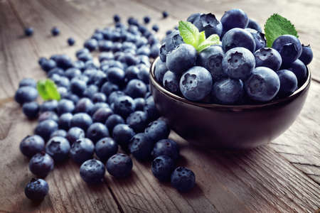 wildberry: Blueberry antioxidant organic superfood in a bowl on a rustic table concept for healthy eating and nutrition