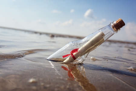 corked: Message in a bottle washed up on a beach concept for help, sos, emergency and assistance