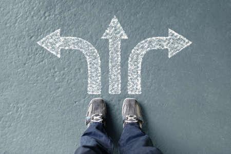 Podejmowanie decyzji na przyszłość człowieka stojącego z trzema strzałkami kierunkowymi wyborów, w lewo, w prawo lub przesunąć do przodu