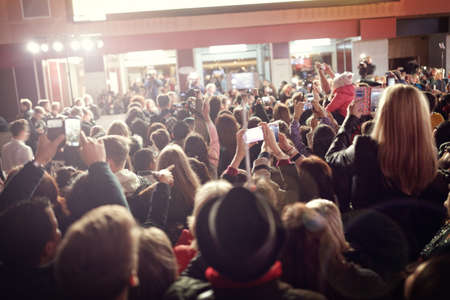 Crowd and fans taking photographs on mobile phones at a red carpet film premiere 版權商用圖片 - 61386067