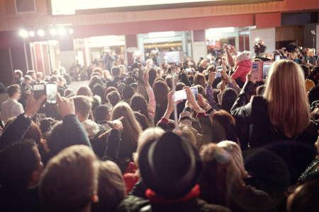 Multitud y los aficionados que toman fotografías de los teléfonos móviles en un estreno de cine alfombra roja