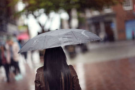 Rain drops falling on a woman holding a black umbrella in a shopping street scene concept for bad weather, winter or protection Stock Photo