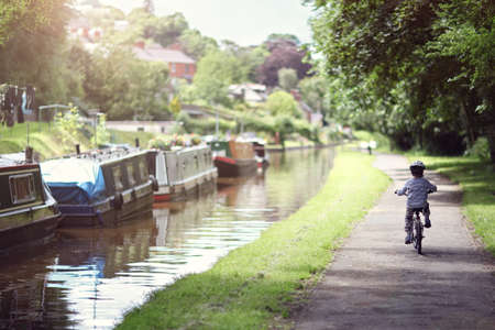 healthy path: Riding a bicycle on a tow path by a canal concept for healthy lifestyle, exercising and vacations Stock Photo