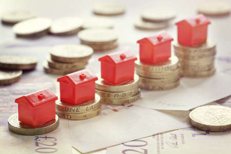 Minature houses resting on pound coin stacks concept for property ladder, mortgage and real estate investment Imagens