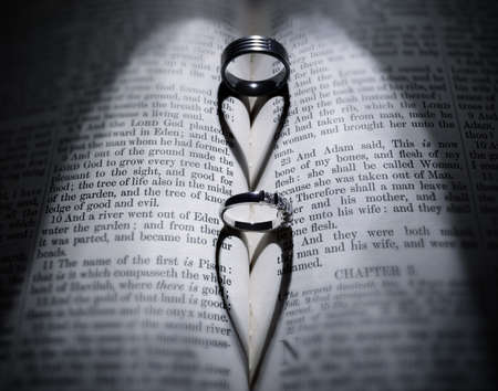 registry: Wedding rings casting heart shaped shadow over Bible