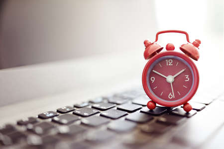 Alarm clock on laptop concept for business deadline, schedule and urgency