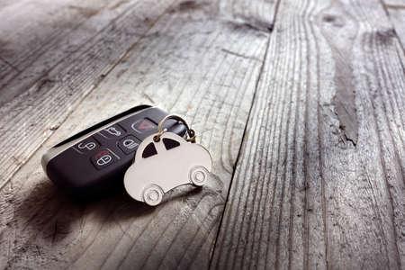 Car shape keyring and keyless entry remote on wood background