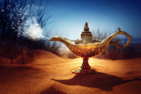 Magic lamp in the desert from the story of Aladdin with Genie appearing in blue smoke concept for wishing, luck and magic