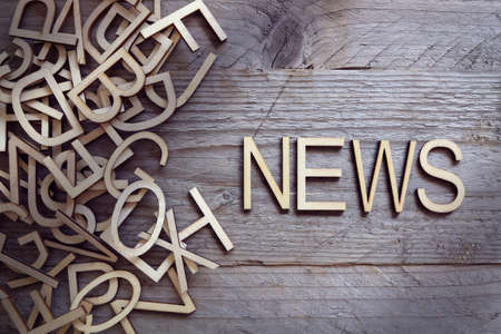 News and media concept wood letters on wooden background