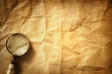 Vintage magnifying glass on old parchment paper background Archivio Fotografico