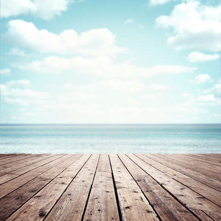 Summer vacation background wooden plank boardwalk with sea and blue sky copy space