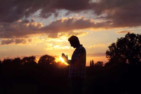Silueta de un hombre orando en el concepto de la puesta del sol por la religión, el culto, la oración y la alabanza Foto de archivo - 66939278