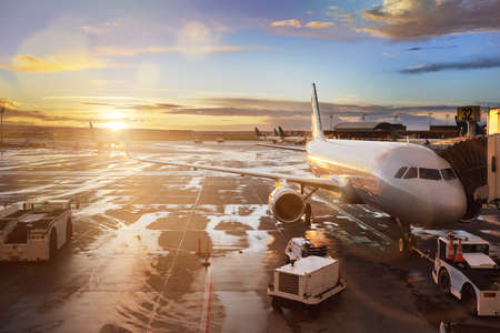 Airplane being preparing for takeoff at terminal gate in international airport at sunrise Stock Photo