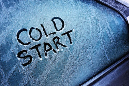 Cold start message written on frozen car windshield window Stock Photo