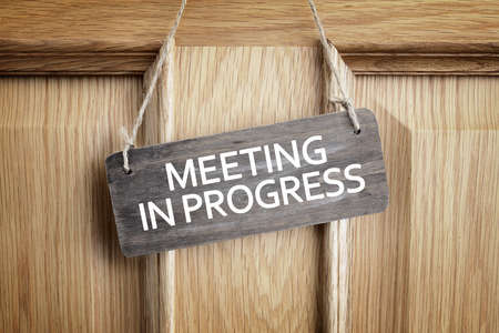 Meeting in progress sign on office door concept for business team staff strategy meeting Lizenzfreie Bilder