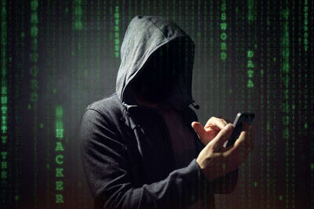 Computer hacker with mobile phone smartphone stealing data Фото со стока
