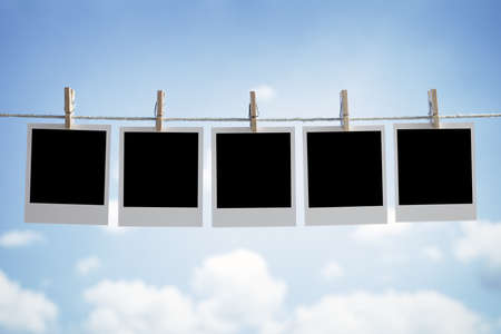 Blank instant print transfer photographs hanging on a clothesline in front of a blue sky
