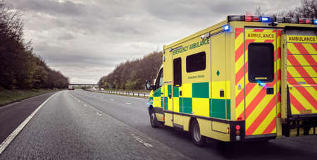 British ambulance responding to an emergency in hazardous bad weather driving conditions on a UK motorway Stok Fotoğraf - 80025270