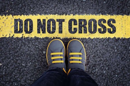 Do not cross line child in sneakers standing next to a yellow line with restriction or safety warning Lizenzfreie Bilder