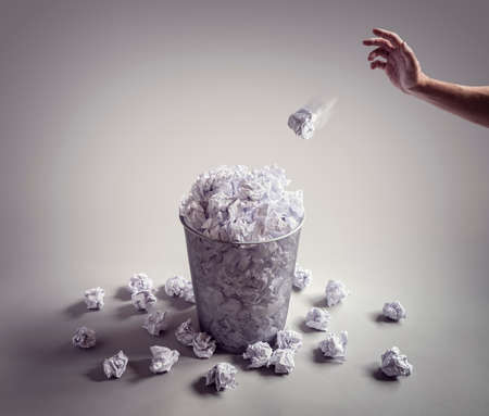 Throw it in the waste paper basket or bin concept for business frustration, stress and writers block Foto de archivo