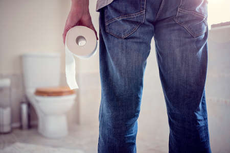 hemorrhoid: Man holding toilet tissue roll in bathroom looking at loo