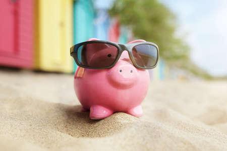 Sparschwein auf Sandstrandurlaub mit Sonnenbrille und Badeboxen