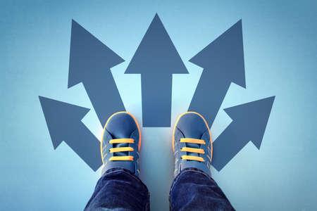 Tomar decisiones para el futuro niño de pie con muchas opciones de flechas de dirección, izquierda, derecha o avanzar Foto de archivo