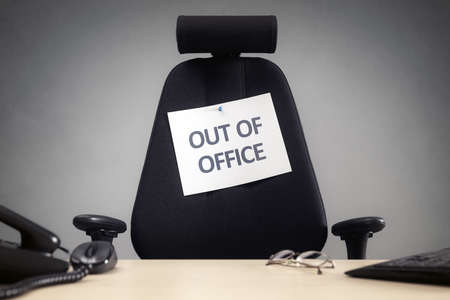 Business chair with out of office sign concept for vacation, holiday, lunch break or work life balance Foto de archivo