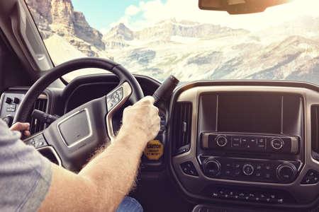 Mens die het stuurwiel houdt die een auto of een vrachtwagen op een landelijke weg door de bergen drijft Stockfoto