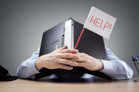 Frustrated and overworked businessman burying his head uner a laptop computer asking for help