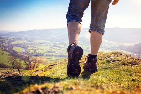 Hiker hiking on a mountain trail with distant views of countryside in summer sunshine Lizenzfreie Bilder
