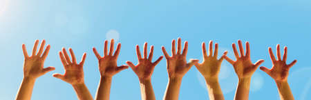 Raised hands on a blue sky background with copy space