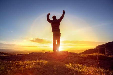 Happy man celebrating winning success or worship and praise against sunset