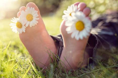 Kind mit Gänseblümchen zwischen den Zehen, die in der Wiese liegt, die im Sommersonnenschein sich entspannt
