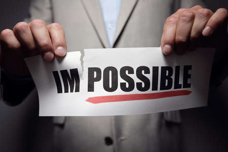 Businessman tearing the word to make possibe concept for self belief, positive attitude and  motivation Lizenzfreie Bilder