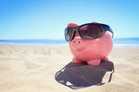 Piggy bank with sunglasses on the beach at the seaside Lizenzfreie Bilder