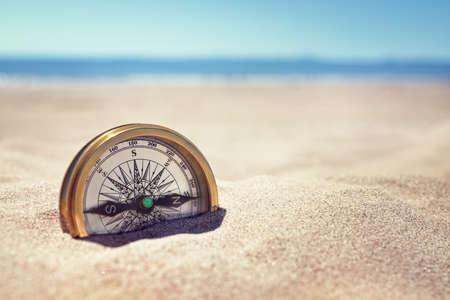 失われたビーチ コンセプトに砂に埋もれている黄金の羅針盤や方向 写真素材